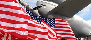 American Flags Flying Behind the tail of a Large Jet Plane